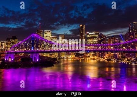 Vibrant night time panorama of Brisbane city with purple lights on Story Bridge, Australia - Stock Photo