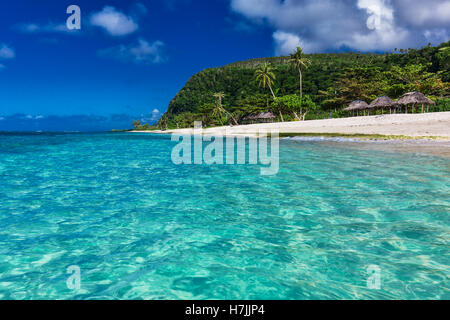 Tropical vibrant natural beach on Samoa Island with palm trees and wooden fales - Stock Photo
