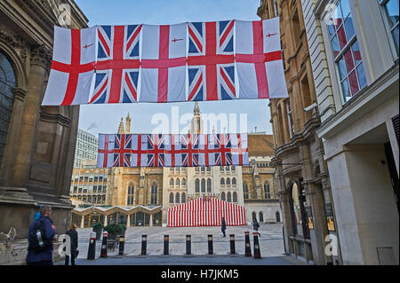 Union Jack flags and the flag of  City of London suspended across a street near to the Guildhall - Stock Photo