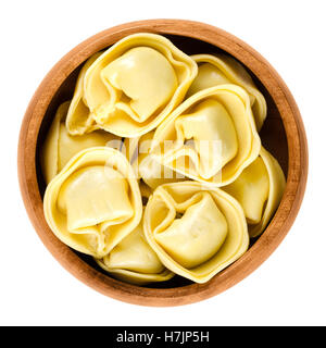 Tortelloni pasta in wooden bowl. Ring-shaped stuffed Italian dumplings with same shape as tortellini, but larger. - Stock Photo