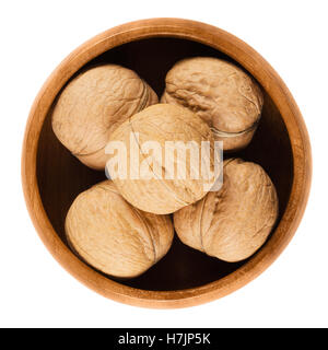 Whole walnuts with shells in a wooden bowl on white background. Brown dried nuts of common walnuts, Juglans regia. - Stock Photo