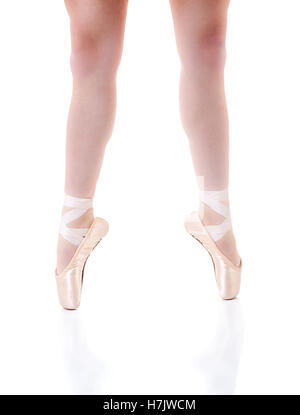 Focus on young ballerina's legs wearing pointe shoes with reflections. Isolated on white with copy space. - Stock Photo