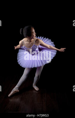 Young Ballerina wearing pointe shoes and tutu in dance pose. - Stock Photo