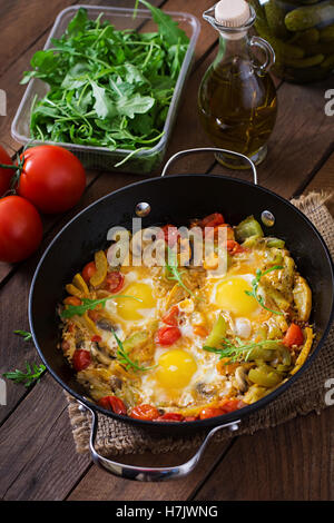 Fried eggs with vegetables in a frying pan on a wooden background. - Stock Photo