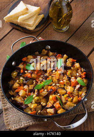 Italian Caponata with frying pan on a wooden background. - Stock Photo