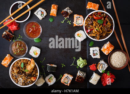 Traditional Japanese food - sushi, rolls, rice with shrimp and udon noodles with chicken and mushrooms on a dark - Stock Photo