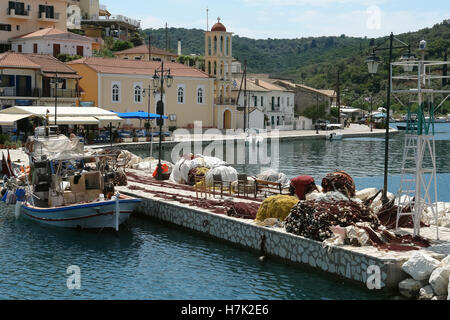 Lefkada, GREECE, May 11, 2013: Landscape with church, mooring and fishing-boat in port of Vathi on the small Meganisi - Stock Photo