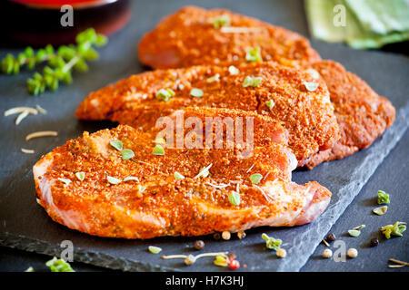 Three marinated pork chops on a slate plate - Stock Photo