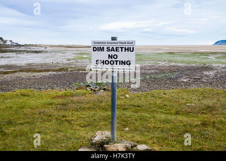 Bilingual 'No Shooting' sign in Welsh and English on salt marsh habitat in Red Wharf Bay (Traeth Coch) Isle of Anglesey - Stock Photo