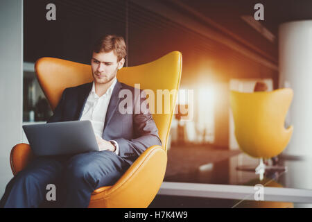 Young serious successful man entrepreneur in formal business suite with a beard sitting on yellow armchair working - Stock Photo