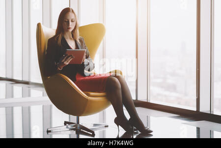 Young serious successful woman entrepreneur in a red dress and jacket sitting on yellow armchair with tablet - Stock Photo