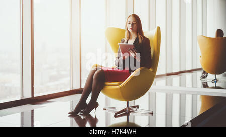 Young serious successful woman entrepreneur in a red dress and jacket sitting on yellow armchair, working on tablet - Stock Photo