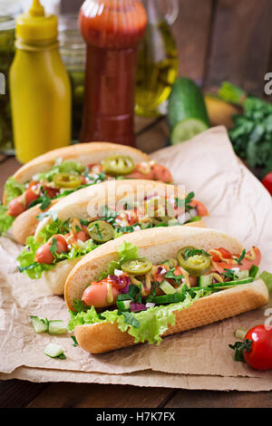 Hot dog with jalapeno peppers, tomato, cucumber and lettuce on wooden background. Top view - Stock Photo