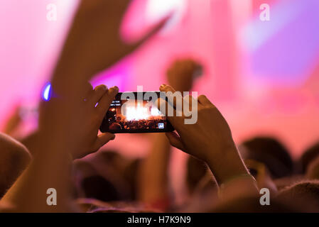 Visitor records live concert using smartphone - Stock Photo