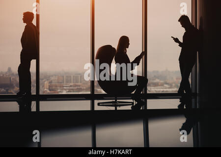 Silhouettes of business  people two man and one woman resting and waiting for the meeting near big window in luxury - Stock Photo