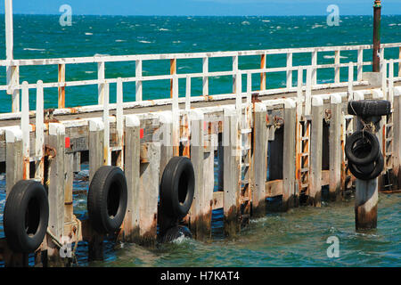 Beach jetty / pier with car tyres to stop the boats from hitting the pillars. Australia. - Stock Photo