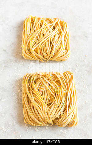 Raw uncooked homemade italian pasta tagliatelle (chinese egg noodles) over rustic white stone background with copy - Stock Photo