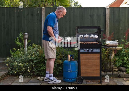 Mature man cooking on a BBQ - Stock Photo