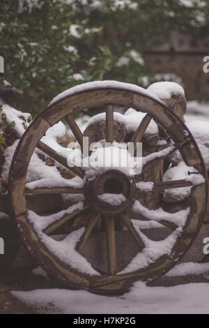 Old vintage wood wagon wheel covered with snow - Stock Photo