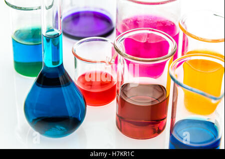 various beakers with different types of indicators in acids and basis, four colors of indicators in several solutions - Stock Photo