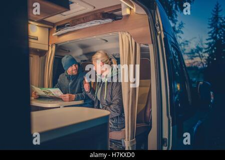 Couples and the RV Park Camping. Young Couples Planning Next Trip in the Motorhome. - Stock Photo