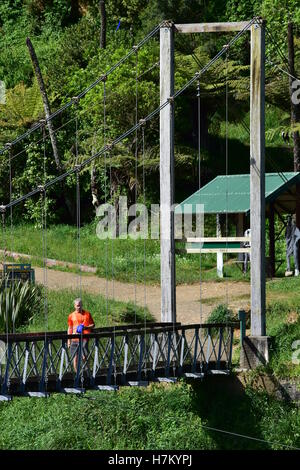 A man walking on the suspension bridge in Karangahake Gorge, NZ. - Stock Photo
