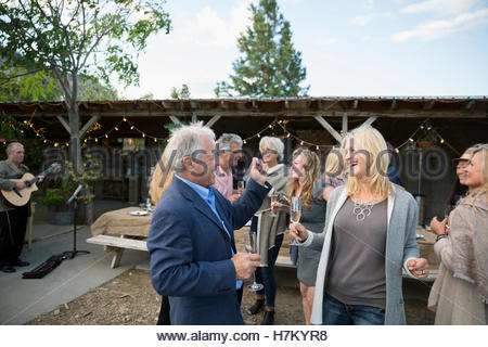 Happy couple dancing and drinking champagne at outdoor party - Stock Photo