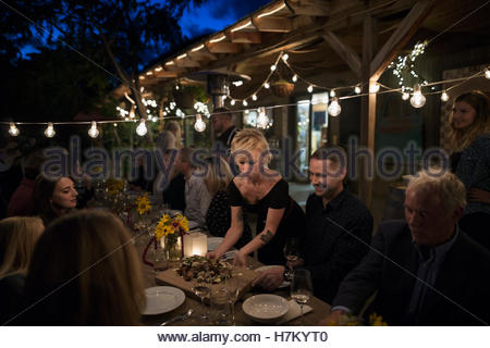 Waitress serving food to friends at outdoor dinner harvest party under string lights - Stock Photo