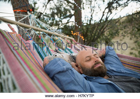 Serene man relaxing in hammock - Stock Photo