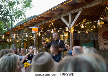 Man leading toast at outdoor dinner party under string lights - Stock Photo