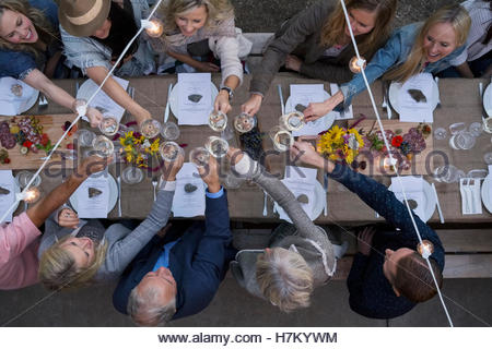 Overhead view friends toasting wine glasses at outdoor harvest dinner party - Stock Photo