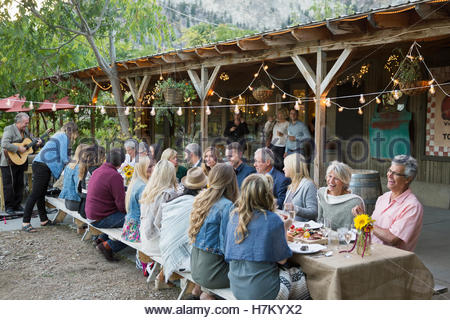 Friends enjoying outdoor harvest dinner party at long patio table - Stock Photo