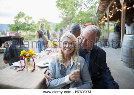 Portrait smiling couple drinking champagne at outdoor dinner party table - Stock Photo