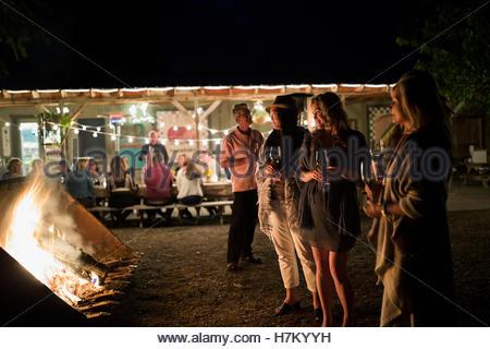 Friends enjoying bonfire and string lights illuminating outdoor dinner party - Stock Photo