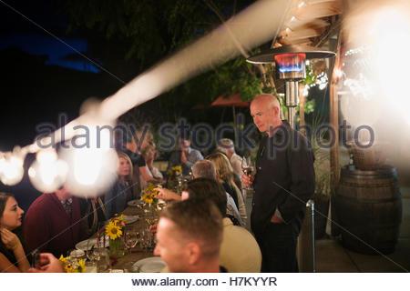 String lights illuminating outdoor patio dinner party - Stock Photo