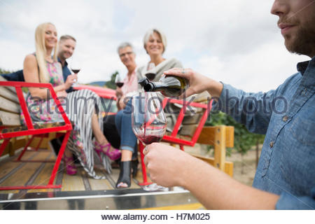 Couples in truck bed wine tasting watching vintner pouring red wine - Stock Photo