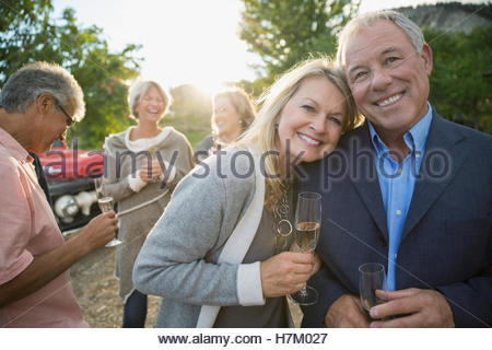 Portrait smiling couple drinking champagne outdoors - Stock Photo