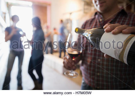 Male vintner pouring red wine in winery barrel room - Stock Photo