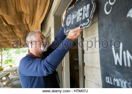 Senior male vintner hanging open sign at winery tasting room - Stock Photo