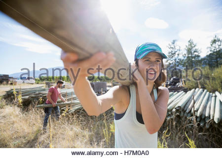 Smiling female farmer carrying wood fence post on sunny farm - Stock Photo