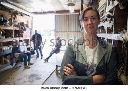 Portrait confident female mechanic with arms crossed in workshop - Stock Photo