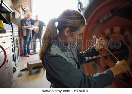 Female mechanic using lug wrench on tractor tire in workshop - Stock Photo