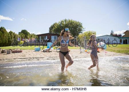 Sisters running and splashing in sunny summer lake - Stock Photo