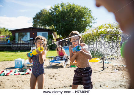 Brother and sister playing with squirt guns at sunny summer beach - Stock Photo