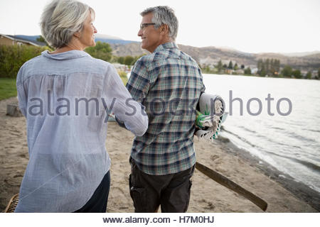 Retired couple walking arm in arm on lake beach - Stock Photo