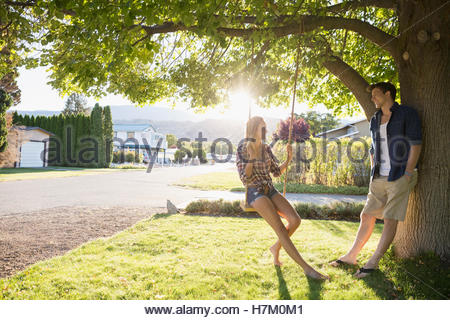 Young couple talking at tree swing in sunny summer yard - Stock Photo