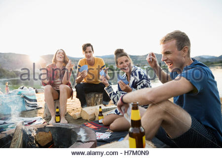 Young couples gesturing playing cards at summer beach campsite - Stock Photo