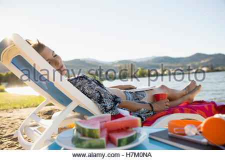 Young woman relaxing napping on lounge chair on summer lake beach - Stock Photo