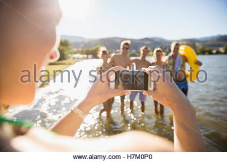 Young woman with camera phone photographing friends at sunny summer lake - Stock Photo
