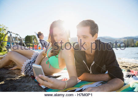 Young couple texting with cell phone on sunny summer beach - Stock Photo